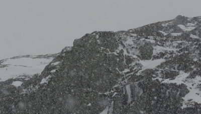 General view of rocky mountains with snow falling