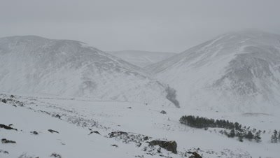 General view of a valley coverd in snow with cloudy skies in the background