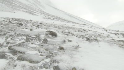 Snow blowing across the frozen, rocky ground
