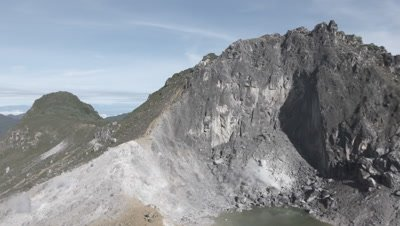 Scenic view of the Sinabung volcano and surrounding mountains from the peak of the Sibayak volcano; steam vent and crater lake visible