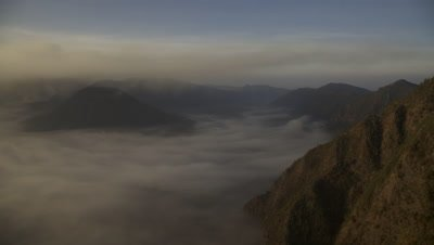 Time lapse of fog and clouds moving over Volcanoes spewing volcanic ash at Bromo Tengger Semeru National Park