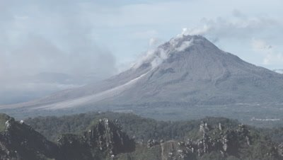 Scenic view of the Sinabung volcano and surrounding mountains from the peak of the Sibayak volcano; steam from a vent on the Sibayak volcano billows into the frame