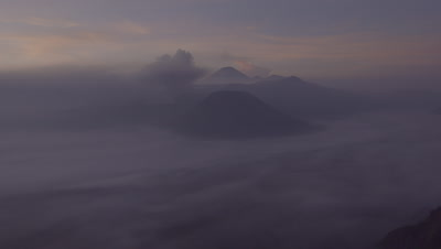 Sunrise over Mount Batok and active volcano Mount Bromo; clouds and ash drifting around the mountains
