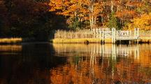 Fall Colors And Reflection On River With Old Dock