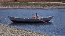 Fisherman Rows Skiff In Small Bay With Black Necked Swans