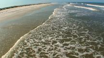 Aerial,Low Over Waves Lapping On Beach