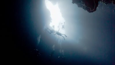 Divers descend into underwater cavern