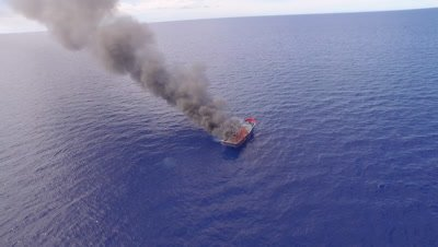aerial drone shot circling a burning illegal fishing boat