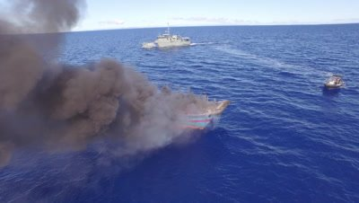 illegal fishing boat burns with marine patrol vessel in background