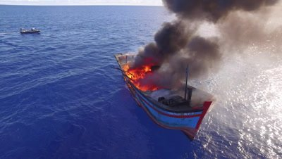 Aerial drone shot of burning illegal fishing boat