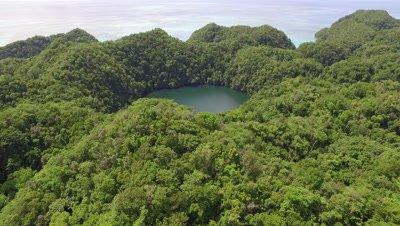 Aerial drone shot over jungle covered island reveals Marine Lake