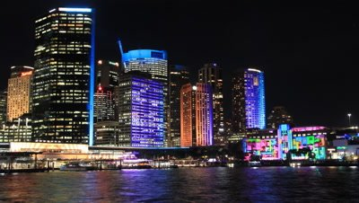 Sydney Australia city scape skyline timelapse shot at night during the vivid festival. The buildings during the Vivid festival have colourful lights that are reflecting of the harbour water.