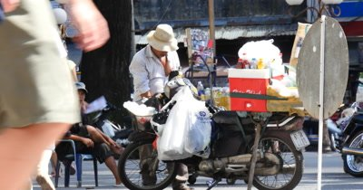 Ho Chi Minh / Saigon Vietnam. Vietnamese city with traffic and crowds of people on the streets of downtown Saigon, Vietnam, traveling on scooters,  cars or walking on sidewalk in this busy metropolitan asian city.