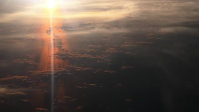 Sunset over the Baltic sea, sun's reflection on the sea with different layers of clouds, aerial view