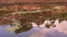 Tranquil Kimberley Water Pool With Water Lily Pads And Reflections Of Rocks And Clouds