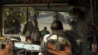 Mid shot roadside barber's shop chair with clients coming and going in foreground and busy traffic in the background in Jaipur,India