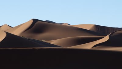 Wide angle desert dune landscape as shadows move across throughout day ending in darkness
