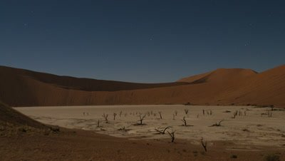 Wide angle curved pan of orange sand dunes with dead trees and contrasting white sand as shadow moves across and evening becomes night with stars in sky