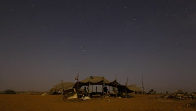 Medium wide angle night falls over Tuareg desert nomad tent and stars move through the sky