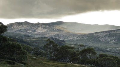 Rays of sunlight sweep over the land in the Snowy Mountains, Australia. The earth looks bleak and empty but the sun brings hope.