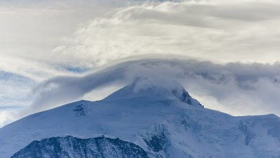 Clouds moving over a mountain on a sunny day