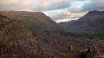 The view from the site of Dinorwig Power Station, overlooking a slate quarry with the rolling sun passing over.