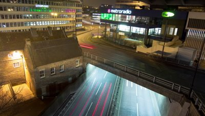 Shot from a rooftop of traffic below on a roundabout and an underpass below.