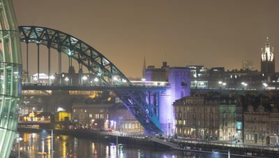 View of the Newcastle Tyne Bridge with the windows of the Sage at the side of frame as traffic passes over the bridge and the quayside below.