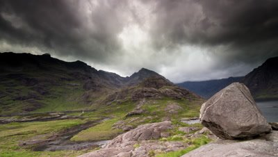 Motion control tracking shot past a rock looking at fast moving gloomy clouds at Loch Coruisk, Isle of Skye