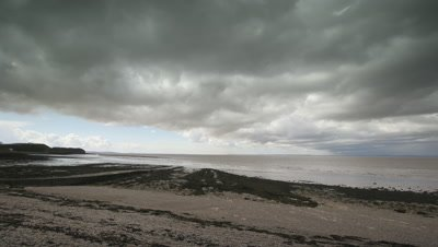 Pan left to right to reveal Clevedon Pier, Somerset, UK while oncoming heavy shower clouds roll overhead.