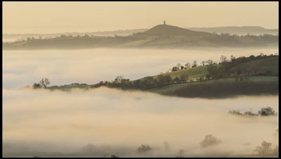 Early morning mist swirling around fields and hillocks with Glastonbury Tor in background. A low lying area known as the Vale of Avalon associated with myth and legend such as King Arthur.