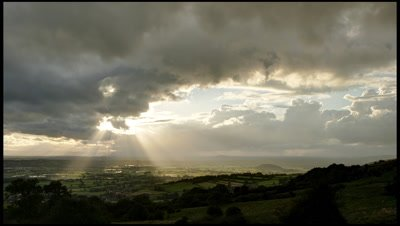 Evening sun and clouds with sun beams rolling towards camera. Overlooking Somerset Levels from high point on Mendip Hills.