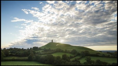 Dawn clouds moving away from camera as sun rises behind Glastonbury Tor, a famous historical and mystical landmark in Somerset, UK