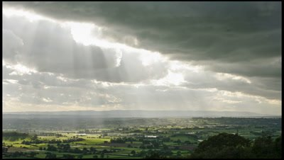 A bank of thick cloud sweeping towards camera with occasional sunbeams shining out towards countryside below. Taken from Mendip hills looking south towards the Somerset Levels, a low-lying region in Somerset, UK