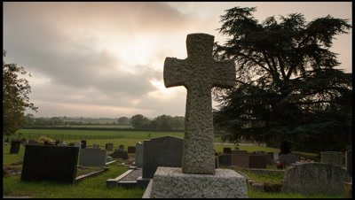 Tracking left to right across graveyard with prominent foreground stone cross as sun rises in background