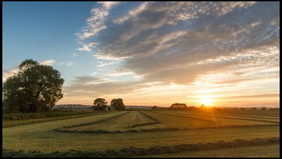Wide angle pan left to right across newly mown hayfield with sun setting in background, Somerset, UK
