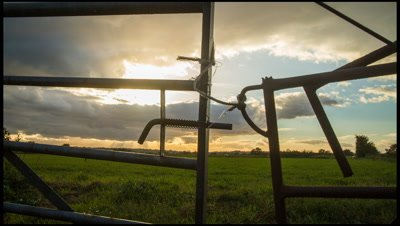 Jib move up with metal stock gate in foreground and fields and sunset developing in background.