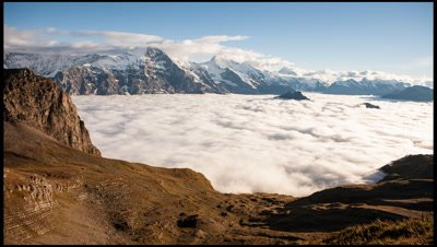 In the Bernese Oberland of the Swiss Alps from Faulhorn overlooking a cloud-filled Grindelwald valley with high alps of Eiger, Monch and Jungfrau in the background and cloud swirling like a tide as the sun sets off camera.