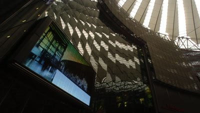 Medium wide angle looking upwards inside the innovative architecture of the highly modern Sony Centre with large tv screen in foreground in Berlin, Germany