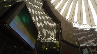 Medium wide angle looking further upwards to ceiling inside the innovative architecture of the highly modern Sony Centre with large tv screen in foreground in Berlin, Germany