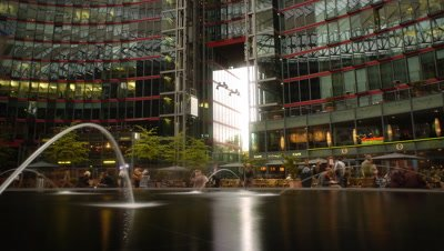 Low angle over pool with fountains inside the innovative architecture of the highly modern Sony Centre busy with people and reflective office windows in the background in Berlin, Germany