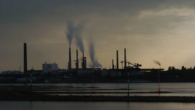 Wide angle factory in lovely early evening light on bank of the River Rhine with billowing smoke plumes, Germany