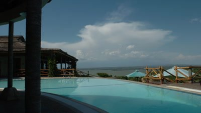 Medium wide angle exterior of Mweya African Safari Lodge swimming pool with grand view over vast savannah landscape in Queen Elizabeth National Park, Uganda