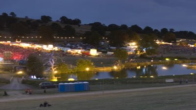 Wide angle panning shot establisher moving over whole festival site ending on the main stage as evening progresses into night at the The Big Chill Festival Ledbury Castle UK