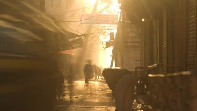 Medium wide angle dimly lit narrow street busy with people, sun swings around to flood scene with golden light and burns out in Jaipur India