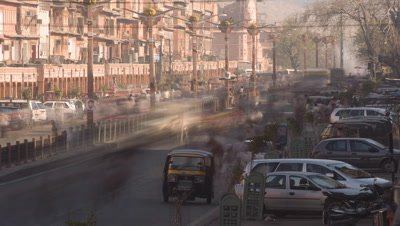 Medium wide angle view over frenetically busy boulevard with attractive buildings and constant streaming pedestrians and traffic in Jaipur India