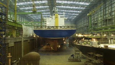 Medium wide angle ship being assembled in large boat shed by robots starts in daylight then changes to artificial lighting in Aker Ship yard Germany