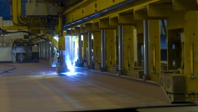 Mid shot welding robot moves towards camera and completes one sequence of welds on steel in Aker Ship yard Germany