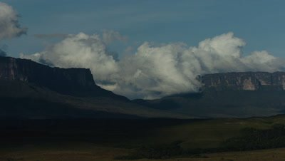 Wide angle boiling clouds move through gap between escarpments at Mt Roraima Venezuela with clear blue sky