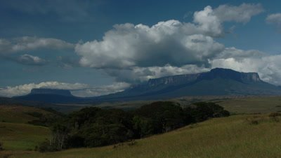 Wide angle establisher of Mt Roraima rising out of the landscape with boiling clouds and blue sky Venezuela